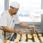 bäcker frittiert berliner in der produktion in bolligen