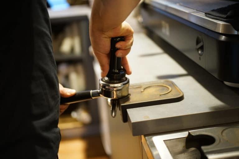 barista am andrücken des kaffees für kolbenmaschine