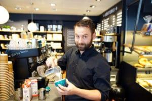 barista in der filiale bubenbergplatz mit cappuccino