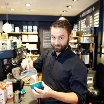 barista in der filiale bubenbergplatz mit appuccino